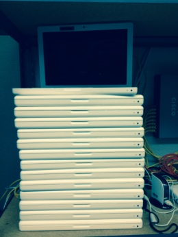 A stack of milky colored school Macbooks with a slight blue tint from filtering. All are closed except for the top macbook which is opened but turned off.