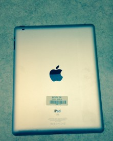 the silver back of a school iPad, showing off the official apple logo.